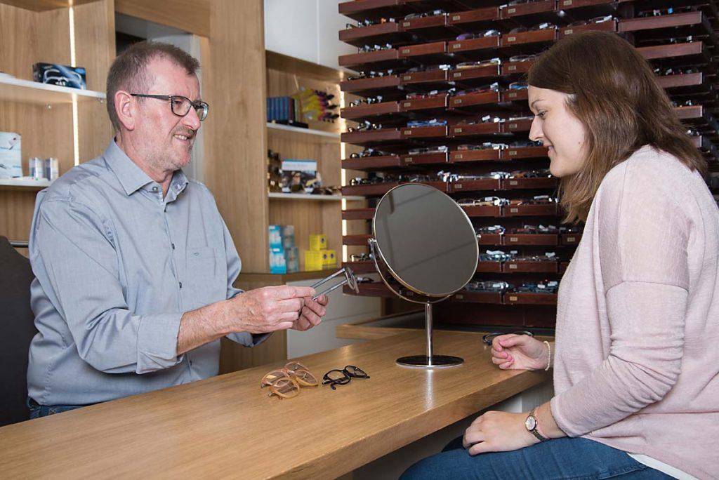 Optiker berät eine Kundin beim Kauf einer Brille