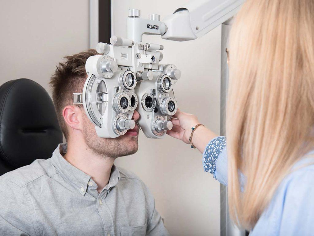 Optikerin misst die Sehstärke bei einem Kunden