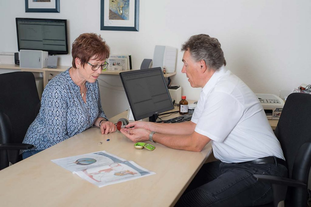 Hörakustiker berät eine Kundin beim Kauf eines Hörgerätes